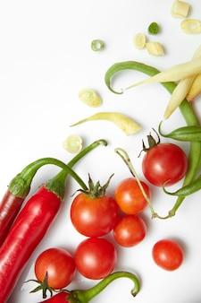 赤唐辛子、黄色と緑の豆とチェリートマト。白いテーブルの上のサラダ。