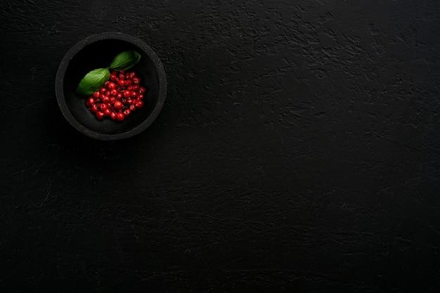 Красный перец в черной миске на белом изолированном фоне