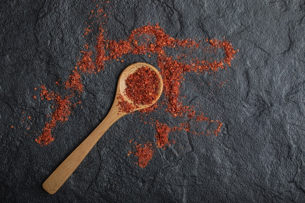Red peppercorns with wooden spoon on black background.