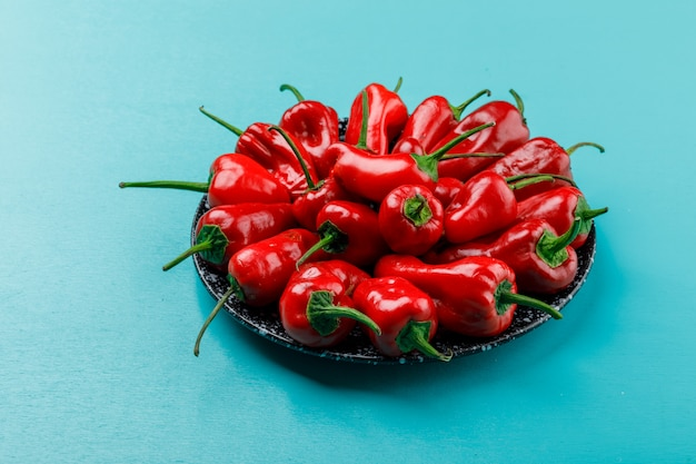 Red peppers in a ceramic dish on blue wall, high angle view.