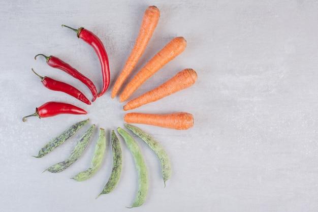 Peperoni rossi, fagiolini e carote su fondo di pietra. foto di alta qualità