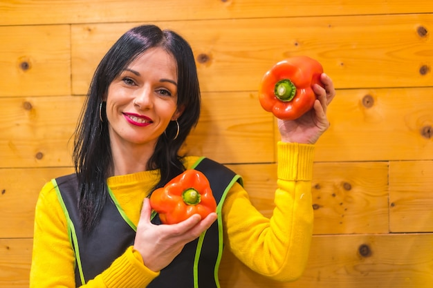 Red peppers in the hand of a brunette caucasian fruit girl, working in a greengrocer establishment