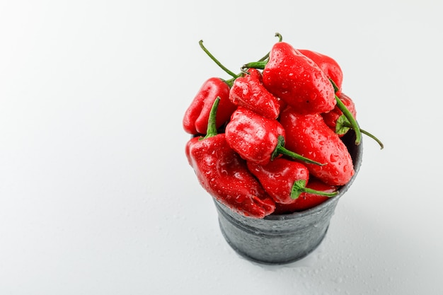 Red peppers in a mini bucket high angle view on a white wall