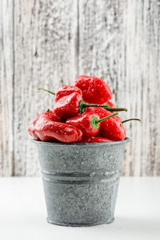 Red peppers in a mini bucket side view on white and wooden grunge wall