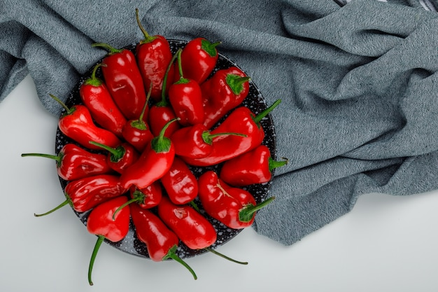 Red peppers in a plate flat lay on white and textile wall