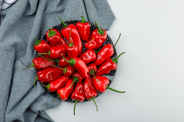 Red peppers in a plate on white and textile wall, top view.