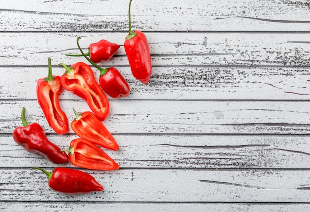 Red peppers top view on old wooden wall