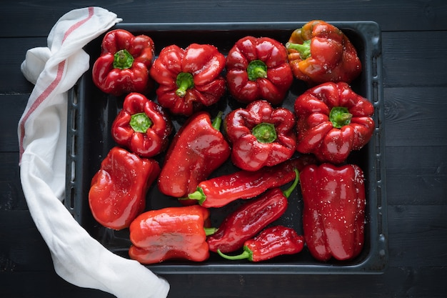 Red peppers on a tray ready to bake.