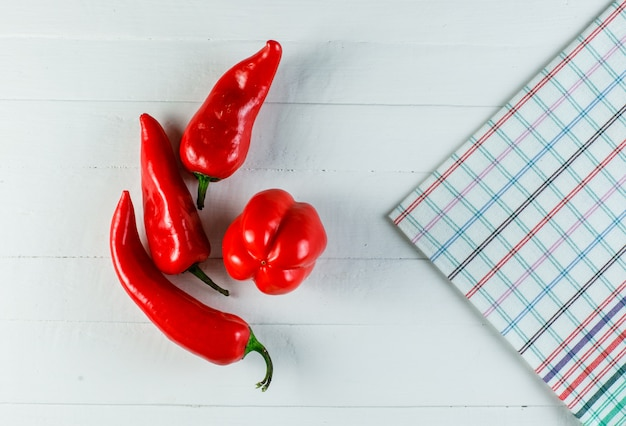 Red peppers with kitchen towel on white wooden surface, flat lay.
