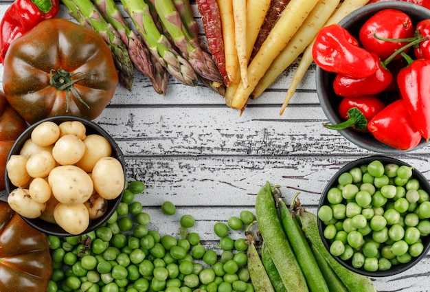 Red peppers with potatoes, tomatoes, asparagus, green pods, peas, carrots in a bowl on wooden wall, top view.