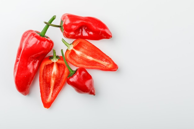 Red peppers with slices on white wall, flat lay.
