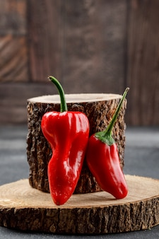 Red peppers with wooden pieces side view on grey and stone tile wall