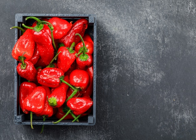 Red peppers in a wooden box on grungy grey wall, top view.