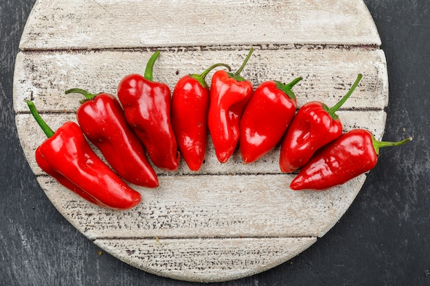 Red peppers in a wooden piece on a dark grunge wall. flat lay.