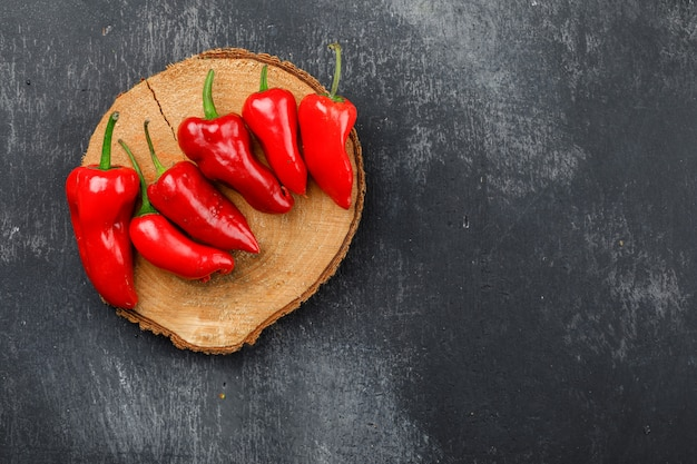 Red peppers on a wooden piece on a dark grunge wall. top view.