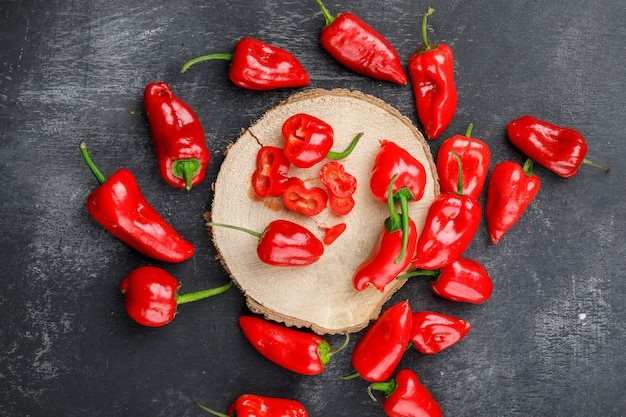 Red peppers on a wooden piece on a grungy grey wall. top view.