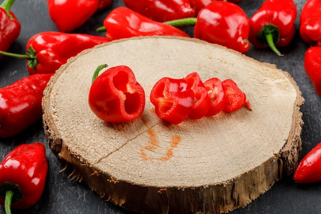 Red peppers on a wooden piece high angle view on a grungy grey wall