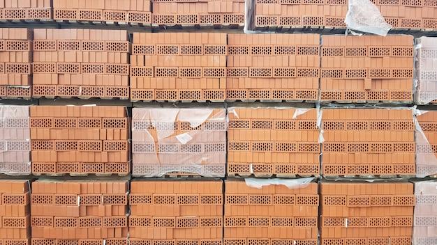 Красный перфорированный кирпич с прямоугольными отверстиями на деревянных поддонах на открытом складе готов к продаже. новые кирпичи на поддонах в строительном магазине.