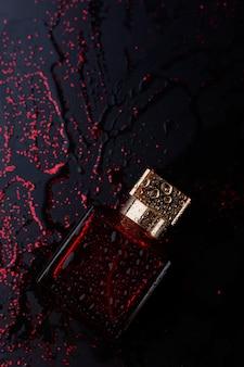 光沢のある黒の背景に赤い香水