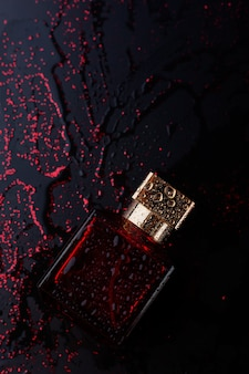 Red perfume on shiny black background