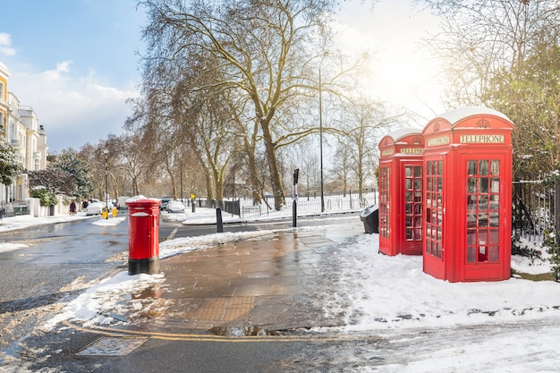 Red phone boxes in london with snow