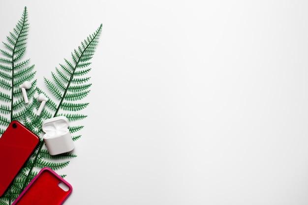 ケース付きの赤い電話とトロピカルグリーンの葉の白い背景にワイヤレスヘッドフォン夏は...