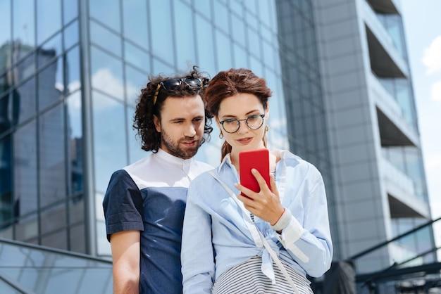 Красный телефон. молодой фрилансер в очках держит в руках красный телефон, стоя перед своим мужчиной