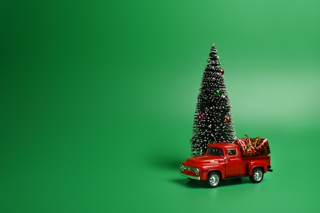Red pickup truck with a christmas tree in the back on an isolated green background.