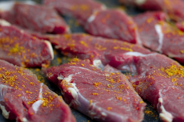 Red pieces of fresh veal with paprika spices, sliced into raw thin beef steaks