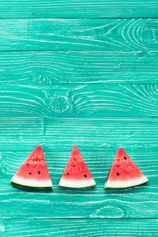 Red pieces of fresh watermelon on green background