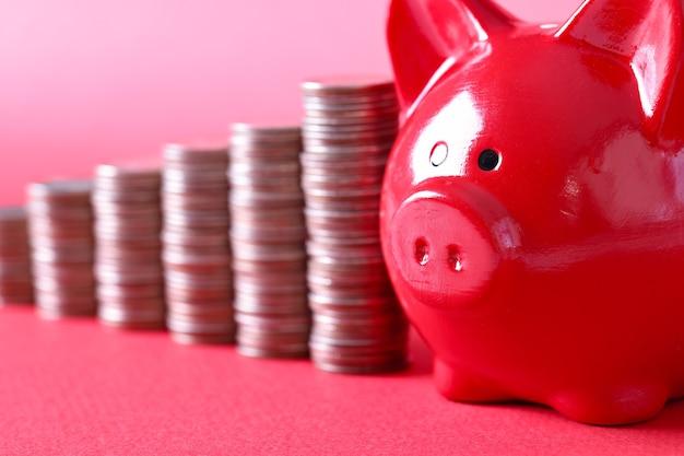 赤豚の貯金箱とコインのスタックは、赤い背景の上に立っています。個人の預金の概念