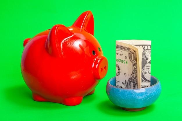녹색 배경에 돈이 있는 파란색 그릇 앞에 있는 빨간 돼지 저금통