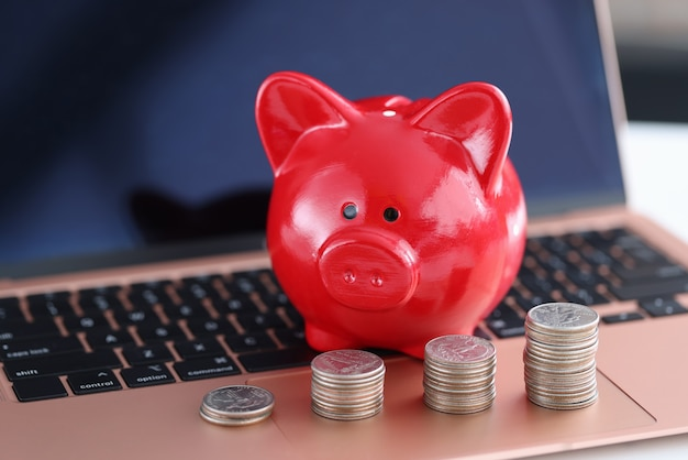 Red piggy bank and coins on laptop keyboard. fast money online concept