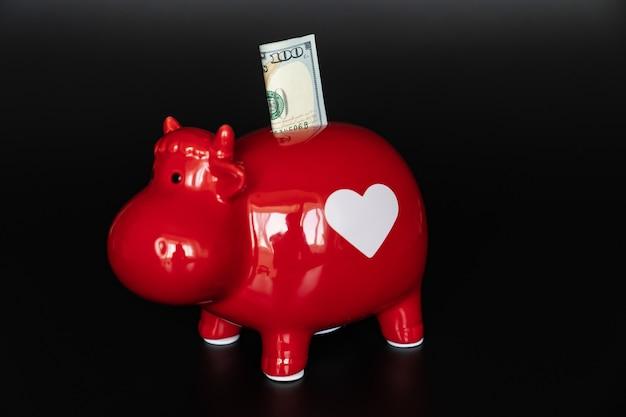 검정색 배경에 100달러가 있는 소 형태의 빨간 돼지 저금통. 돈을 투자하고 저장합니다. 검소함과 금융 지식의 개념.