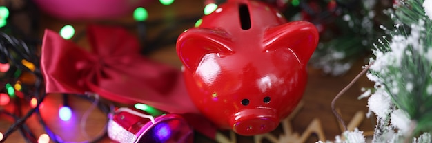 Red piggy bank standing near christmas gifts and tinsel closeup