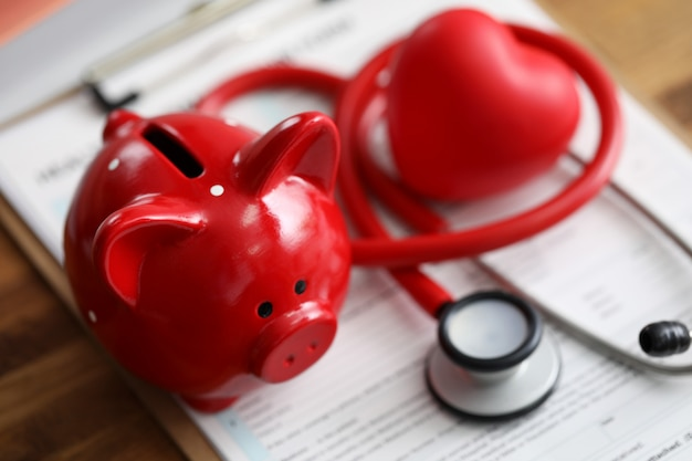 Red piggy bank stethoscope and toy heart lying at health insurance claim application form closeup