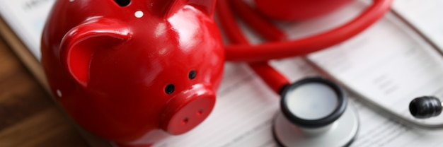 Red piggy bank stethoscope and toy heart lying at health insurance claim form