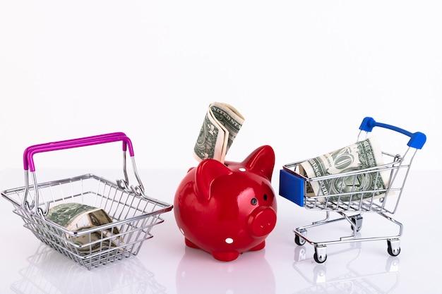 お金とお金の買い物かごが付いている赤い貯金箱。スペースをコピーします。セレクティブフォーカス。危機の概念、食糧不足。