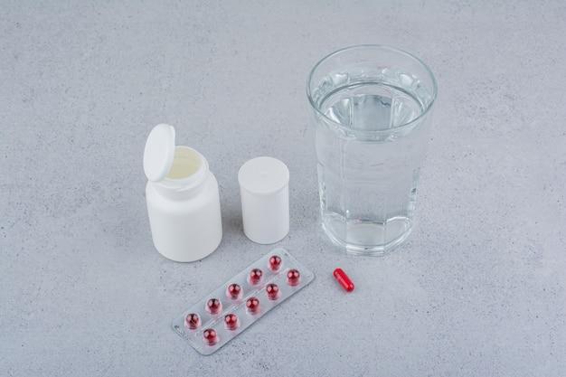 Pillole rosse, contenitori e bicchiere d'acqua sulla superficie in marmo.