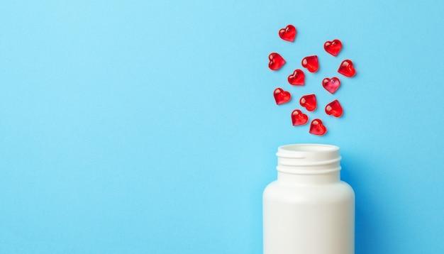 青い背景にボトルとハートの形をした赤い錠剤。テキスト用のスペースをコピーします。