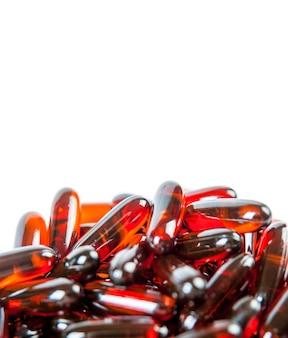 白で分離された赤い丸薬オメガ3-6-9。上面図の画像。テキストのコピースペース。