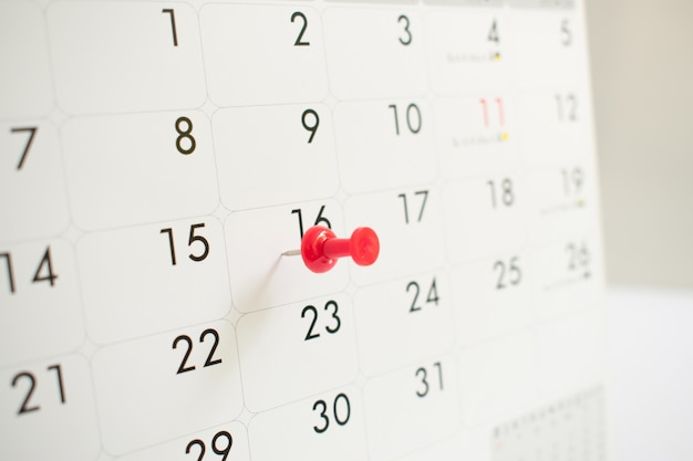 A red pin on the event calendar.background, close up, time