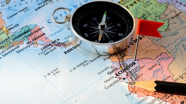Красный флаг штыря помещенный селективный на карте эквадора рики. - экономическая и бизнес концепция.