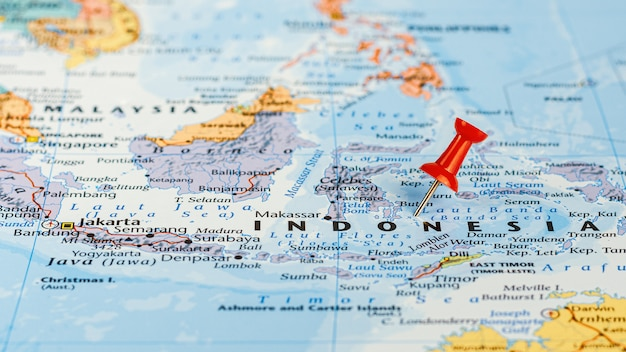 Red pin placed selective at indonesia map. - economic and business concept.