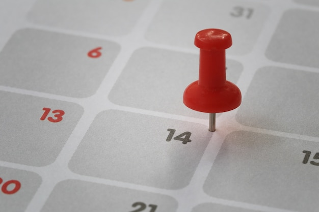 Red pin put on the calendar background in number fourteen concept of valentine's day.