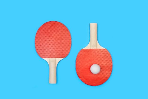 Красные ракетки для пинг-понга и белый шар на синем