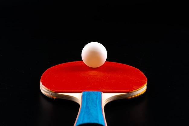 Красная ракетка пингпонга на темной предпосылке. спортивный инвентарь