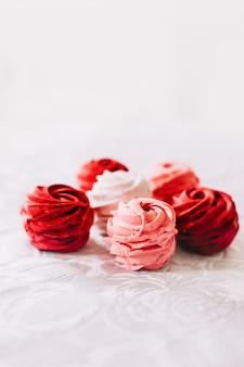 Красный розовый и белый зефир на белом фоне