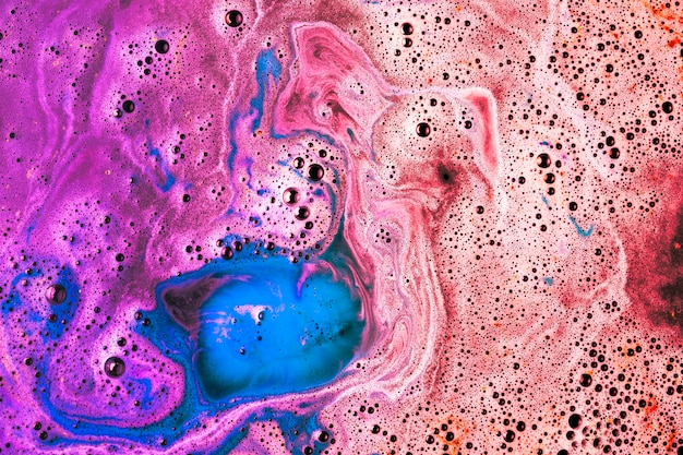 Red; pink; and blue bathbomb dissolve in water