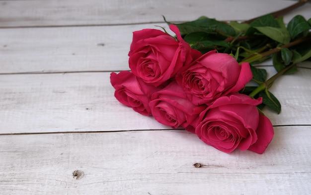 Красно-розовый букет роз на деревянной поверхности